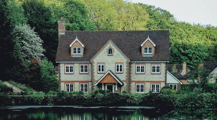 Grande maison devant de l'eau, avec nature en fond