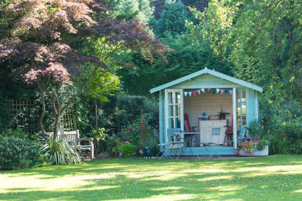 Cabane en bois au fond du jardin d'une maison