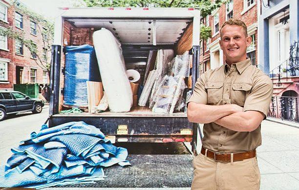 Déménageur professionnel qui se tient devant son camion rempli de cartons avant un déménagement