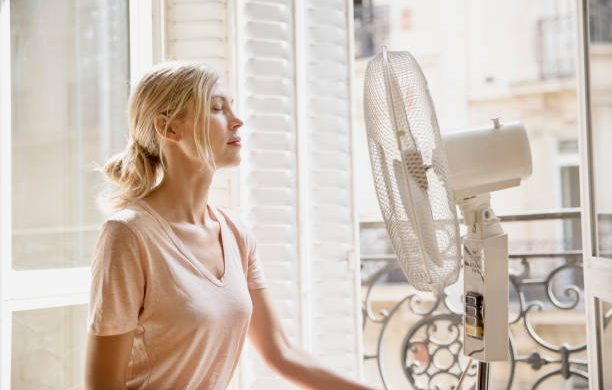 Jeune femme qui utilise un ventilateur pour se rafraîchir pendant la canicule